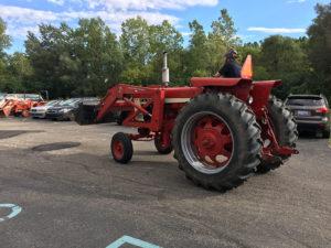 Auto Tech Center auto mechanic riding a red tractor