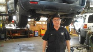Auto Tech Center mechanic inspecting the suspension system of a vehicle