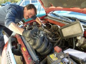 ASE mechanic working on intake manifold