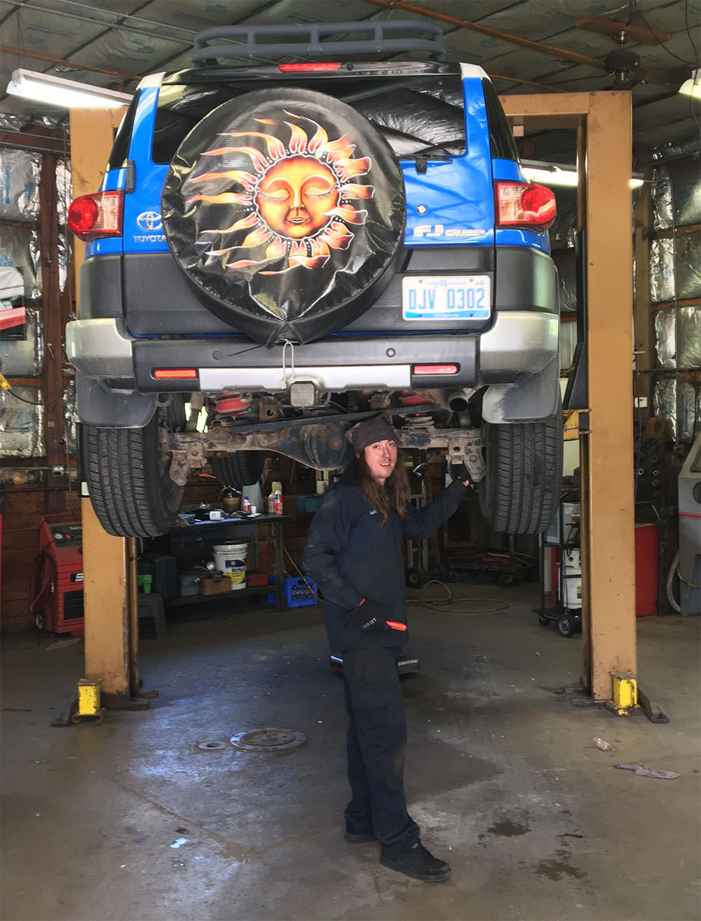 Auto Tech Center mechanic rotating car tires in Ann Arbor MI